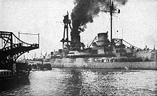 A large warship sits in harbor, smoke pouring from its funnels.