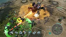 Units battle on a plain. In the bottom left are an assortment of human tanks and helicopters—angular, accented with green. The human units are surrounded by a green circular aura. In the center is a quadrupedal, metallic Covenant vehicle shooting a yellow energy beam at human units.