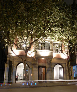 photo of a colonial style building lit up at night. The first two floors of the building are visible, with the top floors obscured by trees with dense foliage. The interior of the gallery can be viewed from outside through two ceiling to floor windows.