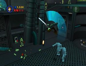 Lego Star Wars: The Video Game - Anakin Skywalker flips over two droids, with several battle droids looking on. Studs, the game's currency, are visible on the overhead ledge and at the far right of the screen.