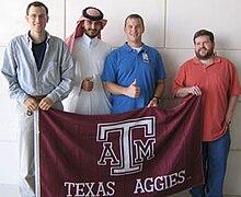 Quatro pessoas em pé atrás de uma bandeira cada um segurando o polegar no ar