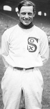 "A man in a white baseball uniform smiles at the camera. He is shown from the knees up. His uniform shows the word ""Sox"", with a small ""O"" and a small ""X"" inside the vertical large letter ""S"". His hands are folded behind his back."