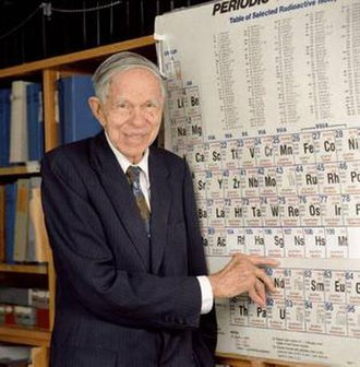 Seaborgium - An aged Seaborg pointing to the element named after him on the periodic table