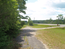 A narrow abandoned road in a wooded area with a two-lane road visible to the right