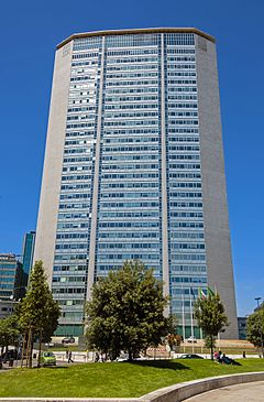 A narrow, unornamented skyscraper with blue-green glass windows in the middle and a tapered metallic skin on the sides rising above some trees at ground level against a blue sky