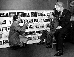 Leopold Stokowski - Walt Disney (kneeling on left) acting out a scene in The Sorcerer's Apprentice segment in Fantasia, with Leopold Stokowski, sitting on the right, and Deems Taylor, sitting second from right.