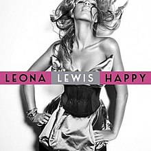"A black and white portrait of a woman. She has a long wavy hair and she is smiling, also she has her hands on her waist. She wears a cocktail dress and many bracelets on her right wrist. In front of her image the words ""Leona"" and ""Happy"" are written in black capital letters and inside a purple box, while ""Lewis"" is in white capital letters appearing in a silver box."