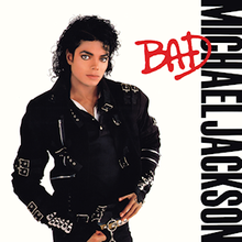 "A man in his late twenties stands and looks forward. His hair is curly and black, he is wearing a black jacket that has several buckles and pants. The background is white and beside him are the words ""Michael Jackson"" in black capital letter, and over them, ""Bad"" in red."