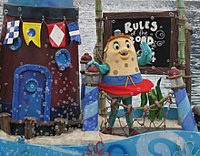A costumed mascot of Mrs. Puff waving to an audience while standing on a float