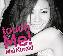 "A young woman, who has her hands up and smiling. The words ""touch Me!"" is written pasted her body in pink."