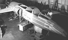 Black-and-white photograph of male personnel working on a wooden mock-up of jet aircraft