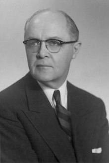 Photographic portait of Adams, wearing a black suit and spectacles