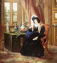 A color picture of an 1833 painting of Lady Tyrconnell sitting in a brown covered chair wearing an 1830s dark blue full dress gown with puffy sleeves, reddish scarf and a dark feathered round hat. She is sitting in the carpeted Gothic style Drawing room next to a brown desk and light red draped window.