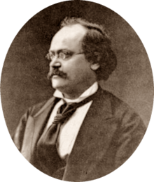 photograph of middle-aged white man with receding dark hair, spectacles and moustache, in semi-profile, facing right
