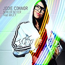 A portrait like a TV Show is Bommerang in a rainbow-like colour of a woman seductively posing with her jacket on her head. The Woman stands hand right and the black stands hand up on the rainbow colour. To the woman's left in black stands 'JODIE CONNOR NOW OR NEVER Feat. WILEY'.