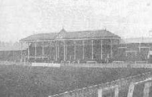 Small Heath - View towards one end of the ground, showing a roof, supported by several pillars and bearing a clock, covering the central part (behind the goal) of an otherwise open terrace