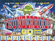 "A bold title in the centre of the image reads ""Thunderbirds Are Go"". A top caption spanning the width of this colourful film poster reads ""Their First Big-Screen Adventure In Colour!"" Between the title and the caption, three rocket-shaped vehicles – one blue, one green and one red – appear to blast outwards from the poster itself. Other images lining the sides of the poster include an exotic pink car, a snake-like rock creature apparently shooting fire from its mouth and, at the base, portraits of some of the principal cast members, who are marionette puppets."
