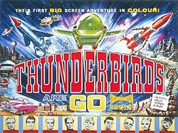 "A bold title in the centre of the image reads ""Thunderbirds Are Go"". A top caption spanning the width of this colourful film poster reads ""Their First Big-Screen Adventure In Colour!"" Between the title and the caption, three rocket-shaped vehicles—one blue, one green and one red—appear to blast outwards from the poster itself. Other images lining the sides of the poster include an exotic pink car, a snake-like rock creature apparently shooting fire from its mouth and, at the base, portraits of some of the principal cast members, who are marionette puppets."
