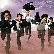 A line of five men in suits, running in the desert.