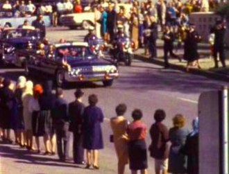 Zapruder film - Frame 150 from the Zapruder film. Kennedy's limousine has just turned onto Elm Street, moments before the first shot, and the President is apparently waving.