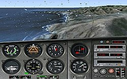 The top half of the image is the view out of a rain-specked airplane windshield, through which a coastline is visible. The bottom half features numerous flight instruments, such as an altimeter and a variometer.