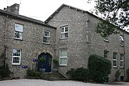 Large grey stone two-story building with a short staircase up to a blue entrance door,