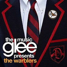 "Close-up of a male private school uniform, showing a white dress shirt with a blue and red blazer and tie. A crest with a styled 'D' as well as a lapel pin featuring a yellow bird are located on the wearer's left. The words ""Glee"", with ""The Music"" above and ""Presents The Warblers"" below, appear to the bottom right in minuscule font."