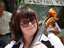 Lani Groves, a caucasian female with dark brown hair, wearing glasses and playing a cello.