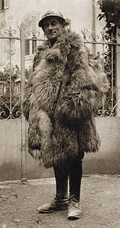 middle aged man in French military uniform wrapped up in fur overcoat