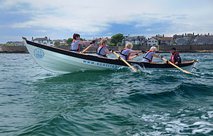Coastal and offshore rowing - A St. Ayles Skiff, a five crew boat during a race at Anstruther in Fife.