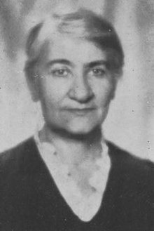 <Black and white portrait photograph of a woman with short, light-coloured hair, wearing a dark dress>