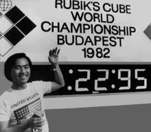 Minh Thai standing next to the timer after setting his 22.95 World Record single