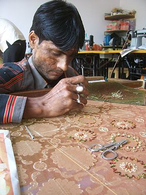 Needlework - In a local fashion boutique in Bangalore, India, a craftsman seen busy with needlework on a designer-ware.