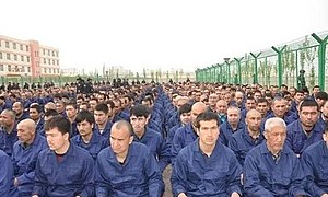 A photo of many Uyghur men, dressed in identical blue clothing, sitting down in rows. On the right hand side of the photo, there is a barbed wire fence. The men are within a re-education camp.