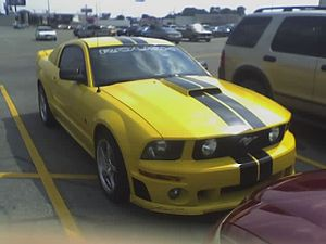 Ford Mustang variants - A yellow Roush Mustang with black racing stripes.
