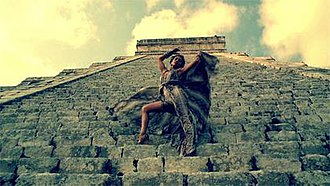 """I'm Into You - Lopez in the music video for """"I'm Into You"""", seen on the steps of a Mayan pyramid, dressed in a snakeskin outfit."""