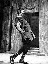 Высокая фигура в тунике, черных штанах и сапогах, в лавровом венке и с выпученными глазами, движется слева направо в преувеличенной позе, голова запрокинута, а живот вытянут вперед.  На заднем плане - ступеньки, ведущие к двери.