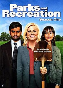 "The DVD cover shows three people standing side-by-side. In the middle, a blond woman wears a gray dress suit, smiling and holding a golden shovel. On the right, a brown-haired woman in a green jacket looks at her and smiles. On the left, a black-haired man with a beard, wearing a gray suit and green tie, looks at the middle figure while smirking. Above the trio is the text, ""Parks and Recreation Season One""."
