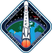 A diamond-shaped emblem with blue borders encasing an artistic depiction of a Falcon 9 rocket launching to space.