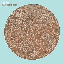 "Pale blue album cover embossed with a brown circle made up from smaller parts. The words ""Hot Chip"" and, below it, ""Made in the Dark"" are displayed in the top left hand corner."