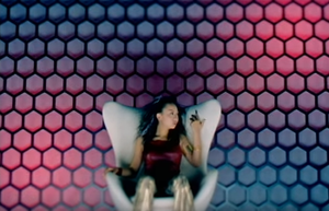 "Take Back - Still from the music video of ""Take Back"", showing Koda seated in front of a multi-coloured LED wall."