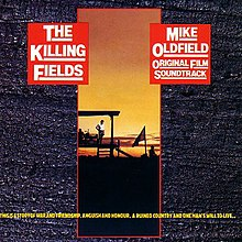 "A rectangular slit on a grey background featuring a sunset photo of a work site. Yellow text is at the bottom of the image; ""This is a story of war and friendship, anguish and honour. A ruined country and one man's will to live..."". Two red squares at the top left and right say the album title The Killing Fields and Mike Oldfield Original Film Soundtrack."