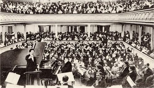Saint-Saens at the piano for his planned farewell concert in 1913, conducted by Pierre Monteux Saint-Saens-farewell-concert-1913.jpeg