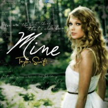 "A blonde woman is standing aside in a white dress, looking forward. Next to her, the word ""Mine"" is written in white. Under the word ""Mine"", the words ""Taylor Swift"" are printed in yellow. Faded lyrics from the songs are above the word ""mine'."