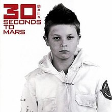 "A boy with short hair. He wears a white jacket with a print on the left arm. In the top left, the words ""30 Seconds to Mars"" and four symbols are written in red font, with the ""30"" in bold."