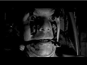 """Axe to Fall - Screenshot from the """"Axe to Fall"""" music video showing a man strapped to a machine with his eyes forced open and tubes sticking out of his mouth."""