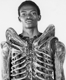 Bolaji Badejo in suit, 1979 by Mike Sibthorp.png