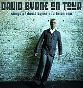 "Tour poster featuring Byrne posing in front of a teal brick wall with stylized text reading ""David Byrne on Tour / Songs of David Byrne and Brian Eno""."