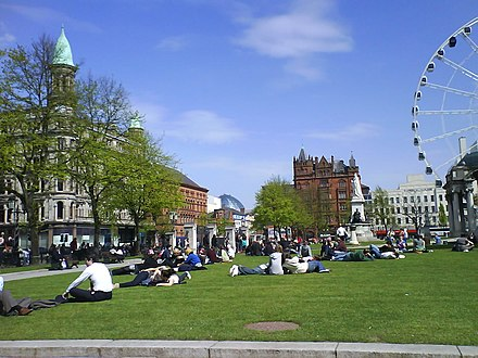 The grounds of City Hall are popular for relaxation during the summer. In the background are the dome at Victoria Square Shopping Centre and the Belfast Wheel. City Hall in summer.JPG