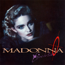 "Portrait of a young blond woman against a black background. Only her face is highlighted. She sports flowing blond hair and blue eyes. Her face looks sombre and she looks a little to the right of the camera. Below her image, the word ""Madonna"" is written in capital letters across the length of the photo. On the bottom-right, the word ""Live to Tell"" is written in flowing pink color."